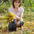 Girl sitting in autumn park - Stock Photo
