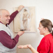 Couple hanging up an art picture on their wall — Stock Photo