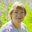 Woman in plant of violet wild lupine — Stock Photo #4111159