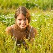 Girl  lying in meadow grass - Stock Photo