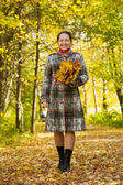 Elderly woman walking in autumn park — Stock Photo