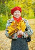 Portrait of mature woman in autumn park — Stock Photo
