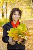 Girl with autumn bouquet in park — Stock Photo