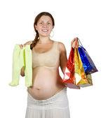 Mulher grávida com roupas do bebê — Fotografia Stock