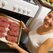 Woman putting stuffed beef  into oven - 