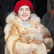 Woman chooses fur coat — Stock Photo