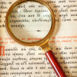 Magnifier  on page of old book - Stock Photo