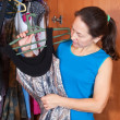 Woman chooses dress in wardrobe — Stock Photo #4615023