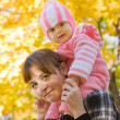 Mother with her baby against autumn — Stock Photo