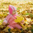 Baby in yellow autumn leaves — Stockfoto