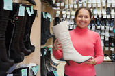 Woman chooses high boots — Stock Photo