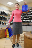 Woman with shopping bags at shoe store — Stock Photo