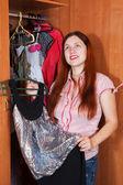 Woman chooses dress in wardrobe — Stock Photo