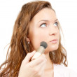 Young woman putting make up on her face. Isolated over white - Foto Stock
