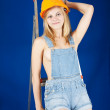Sexy girl in dungarees on stepladder — Stock Photo