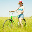 Girl riding bicycle in grass - Stock Photo