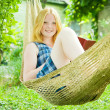 Girl reading book on hammock — Stock Photo