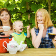 Family having tea  at pergola — Stock Photo
