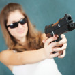 Girl aiming a black gun — Stock Photo