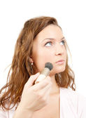 Young woman putting make up on her face. Isolated over white — Stock Photo