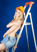 Topless girl in hardhat on stepladder — Stock Photo