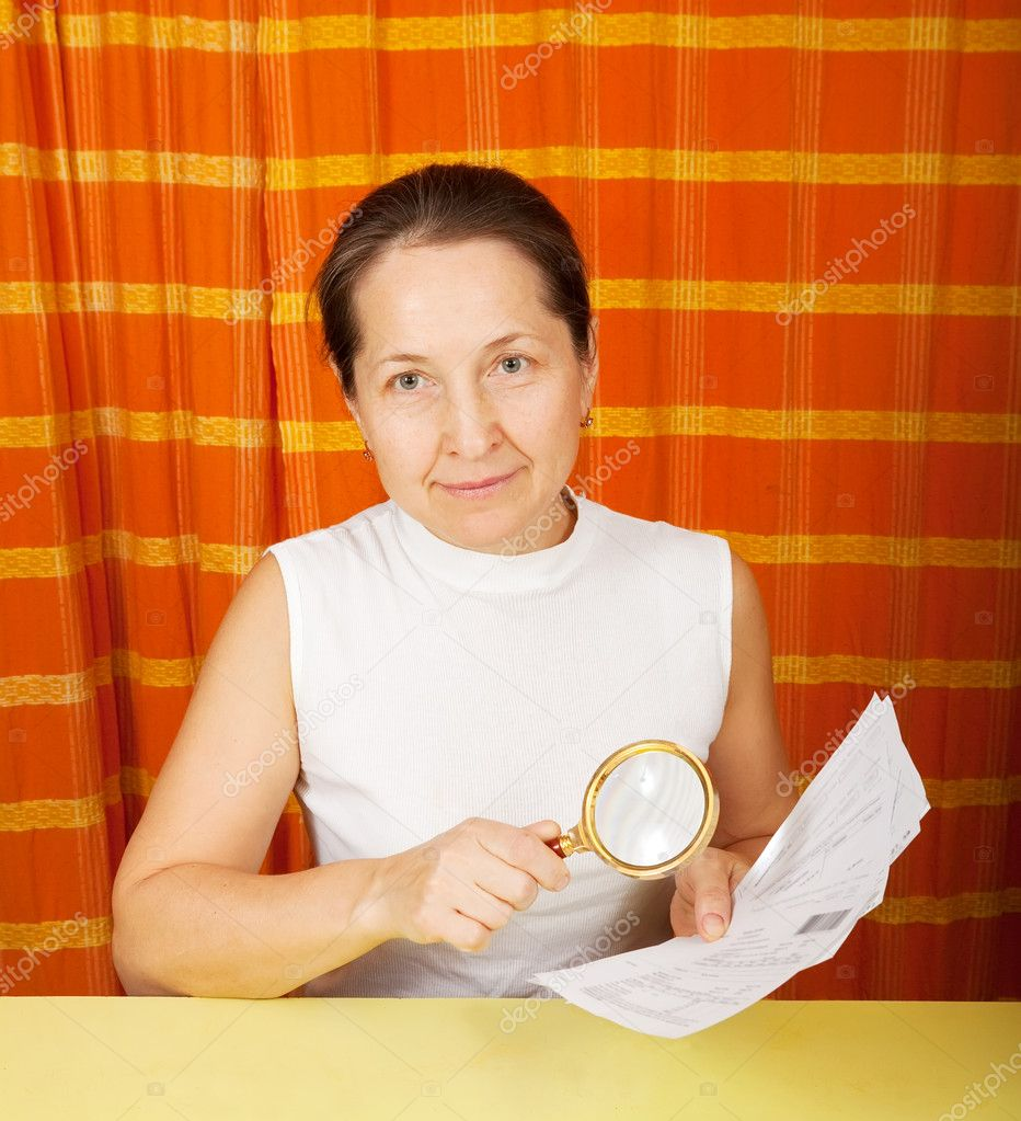 Mature woman looking at utility bills through  magnifier  — Stock Photo #4624393