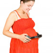 Pregnant woman with headphones on tummy — Stock Photo