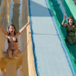 Women in bikini on swimming pool water slide — Stock Photo #4818585