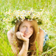 Girl  in camomiles chaplet in grass - Stock Photo