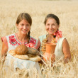 Women with bread at rye field — Stock Photo