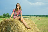 Pretty girl on straw bale — Stock Photo