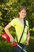 Girl works with grass-cutter — Stock Photo