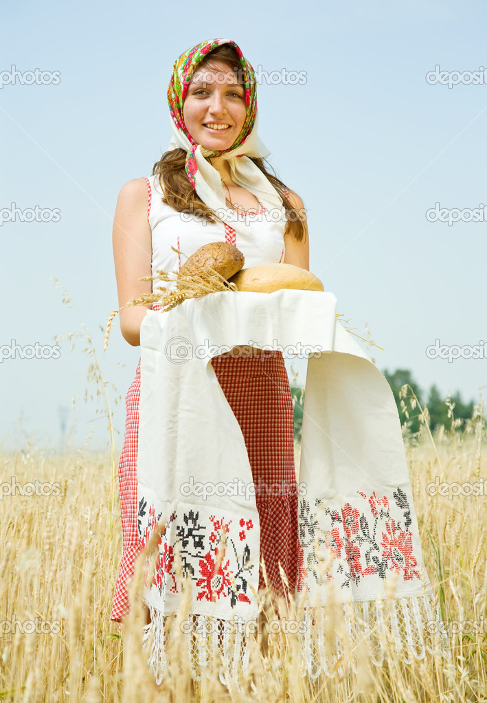 Girl in traditional clothes with bread  at wheat field  Stock Photo #4819759