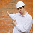 Royalty-Free Stock Photo: Builder   pointing to    brick wall