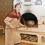 Woman puts a pot into russian stove — Stock Photo