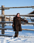Girl in fur coat against winter rural — Stockfoto