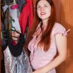 Woman chooses dress in wardrobe — Stock Photo #5149361