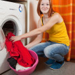 Woman putting clothes into washing machine — Stock Photo
