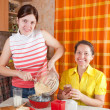 Women making celebration cake — Stock Photo