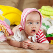 Baby girl with heap of baby's wear — Stock Photo
