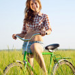 Girl riding bicycle in grass — Stock Photo #5152623