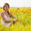 Girl is sitting on flowers meadow — Stock Photo #5152658