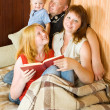 Stock Photo: Family sitting on couch and reading