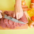 Cook hands cutting beef — Stock Photo
