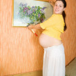 Pregnant woman decorating room with picture — Stock Photo #5153648