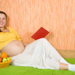 Stock Photo: Pregnant womwith book