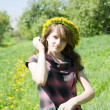 Girl  in a chaplet against a meadow — Stockfoto