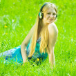 Girl listening music on meadow — Stock Photo