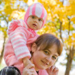 Mother with  baby against autumn nature — Stock Photo