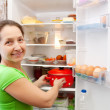 Woman putting pan into fridge - Stock Photo
